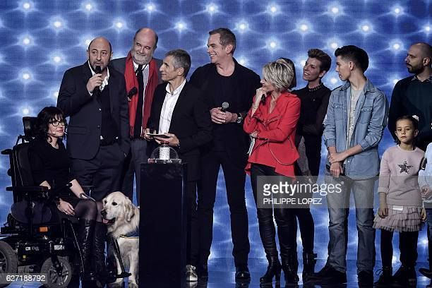 French actor Kad Merad speaks as he is flanked by french TV host Nagui French Canadian singer Garou and French TV host Sophie Davant during the...