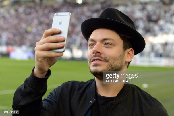 French actor Kev Adams takes pictures with a mobile phone prior to the French L1 football match between Bordeaux and Marseille on May 14 2017 at the...