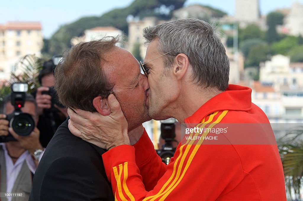 French actor Lambert Wilson kisses French director Xavier Beauvois as they pose during the photocall of 'Des Hommes et des Dieux' (Of God and Men) presented in competition at the 63rd Cannes Film Festival on May 18, 2010 in Cannes.