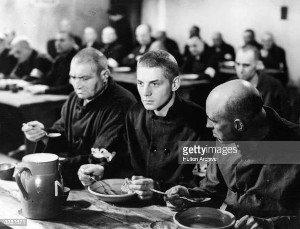 French actor Pierre Fresnay takes a meal with his fellow prisoners in a scene from 'CheriBibi' directed by Leon Mathot for DPF