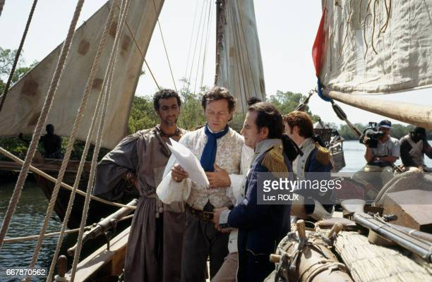 French actor SMayl Mekki actor and director Bernard Giraudeau and actors Richard Bohringer and Thierry Fremont on the set of Giraudeau's film Les...