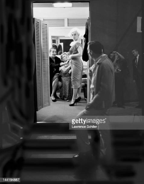 French actor Yves Montand looks through the door of a dressing room belonging to American actress Marilyn Monroe who is being fitted for her costume...