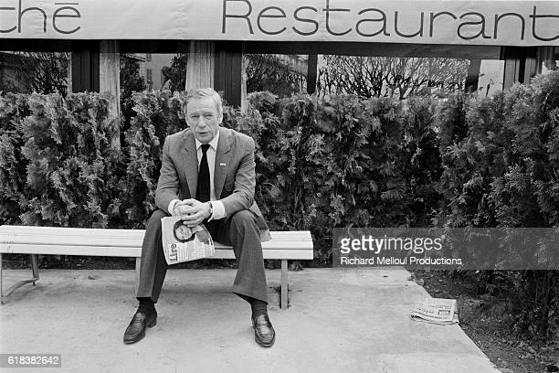 French actor Yves Montand sits on a bench outside a restaurant during the MIP TV fair in Cannes