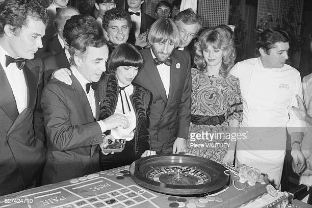 French actors and musicians gather to inaugurate the new roulette table at Casino d'Enghien In front are Actor Charles Aznavour singer Mireille...