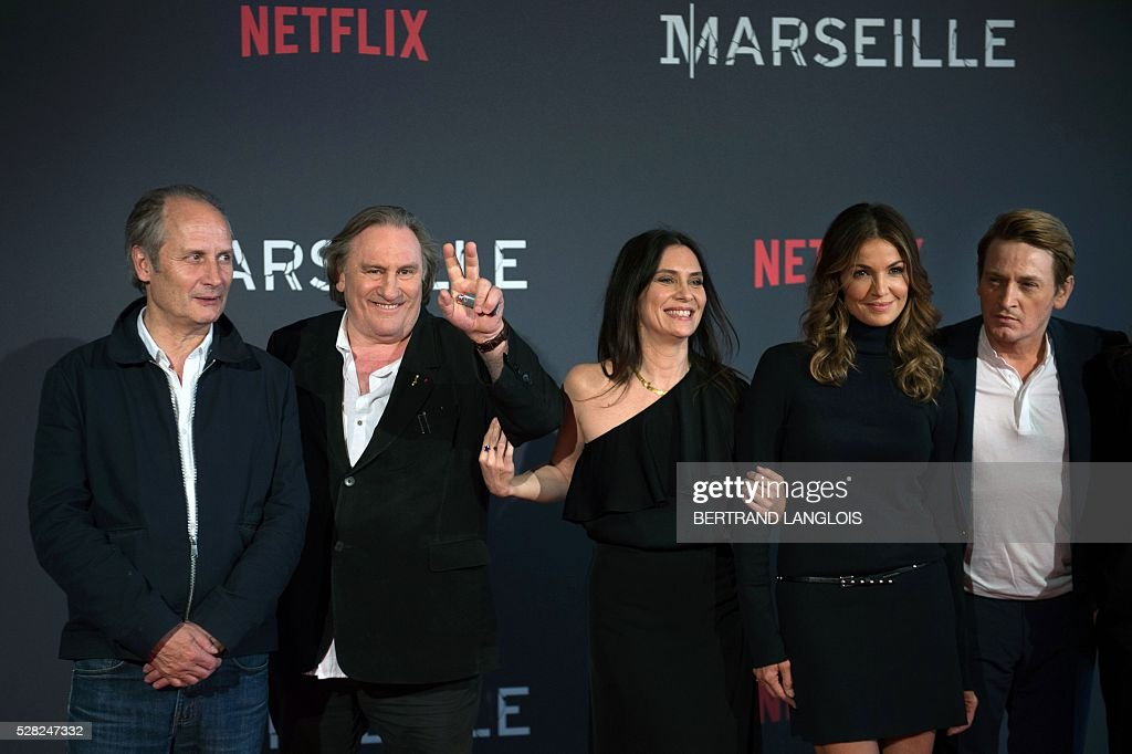 French actors Hippolyte Girardot, Gerard Depardieu, Geraldine Pailhas, Nadia Fares and Benoit Magimel pose with a guest during a photocall for the premiere of the French TV show 'Marseille' broadcasted and co-produced by Netflix on May 4, 2016 in Marseille, southern France. / AFP / BERTRAND