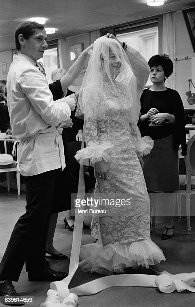French actress Annie Girardot accompanied by Marc Bohan tries on a wedding dress at Dior for the stageplay Apres la Chute written by Arthur Miller...