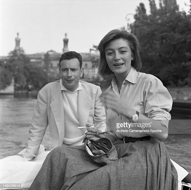 French actress Anouk Aimee portrayed while lighting a cigarette with some matches Alexandre Astruc in the background Lido Venice 1955