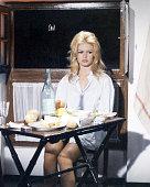 French actress Brigitte Bardot sitting at a folding table wearing a man's shirt circa 1965