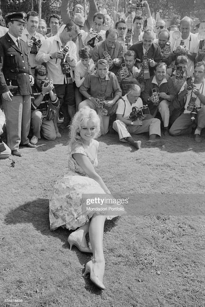 French actress Brigitte Bardot sitting on the grass and being photographed by the journalists at the 19th Venice International Film Festival. Venice, August 1958
