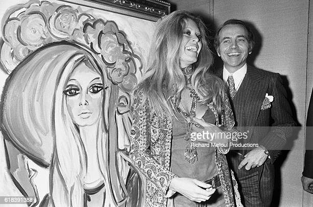 French actress Brigitte Bardot stands next to her portrait by Vincent Roux with French fashion designer Jean Bouquin. Bardot wears shorts, a v-neck halter top and a long jacket.