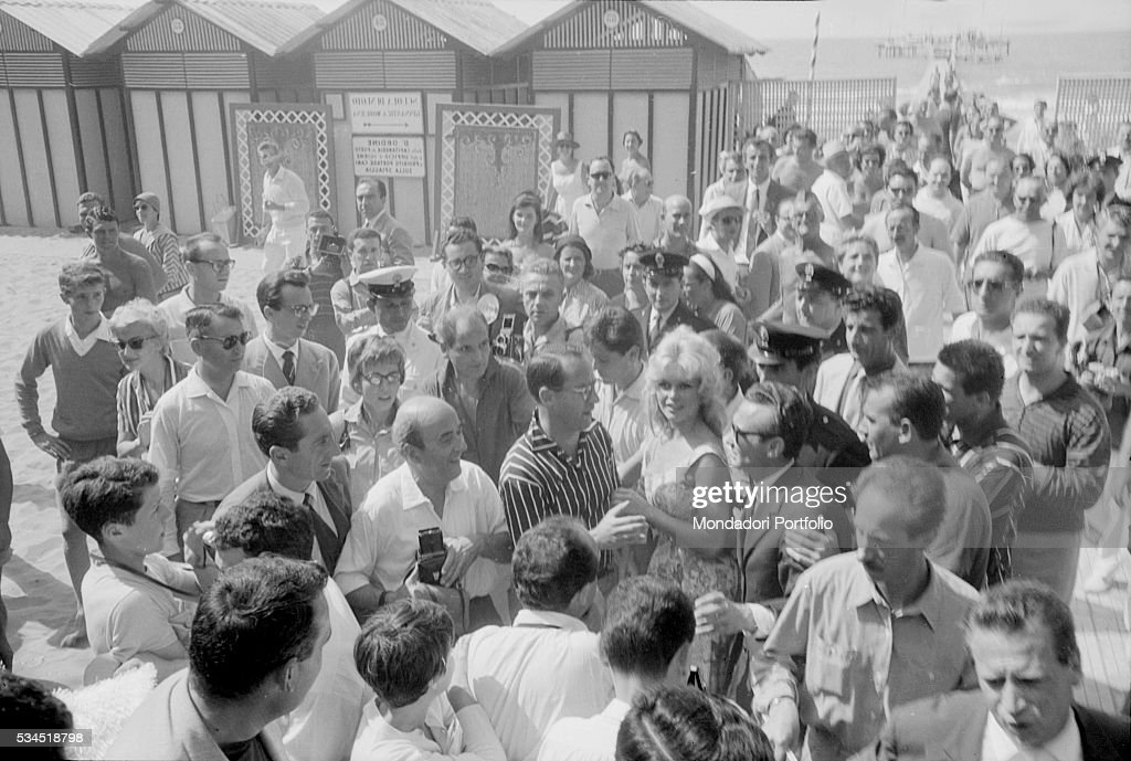 French actress Brigitte Bardot surrounded by the her fans when arriving in a lido at the 19th Venice International Film Festival. Venice, August 1958
