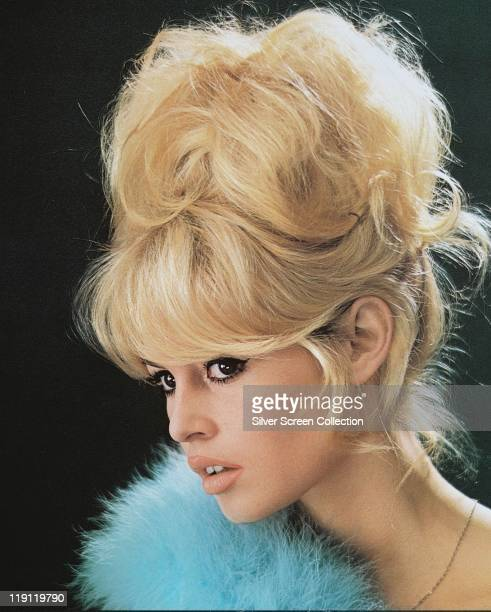 Headshot of Brigitte Bardot French actress model and singer with a bouffant hairstyle and a blue boa in a studio portrait against a black background...