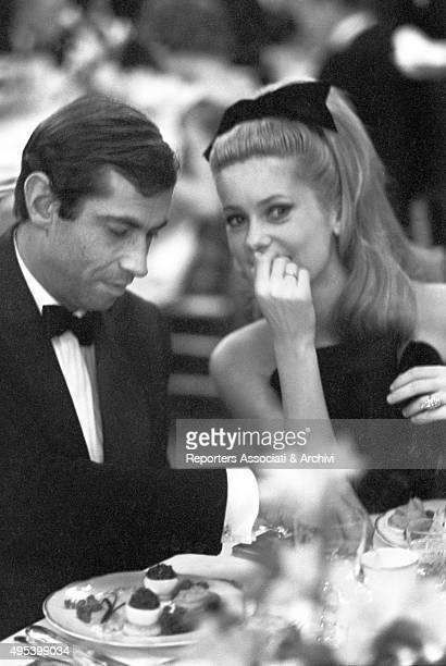 French actress Catherine Deneuve and French actor and director Roger Vadim sitting at the table at the Paris Opera Gala for the presentation of the...