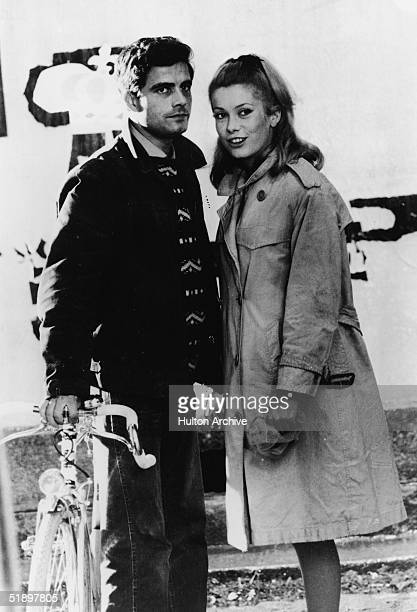 French actress Catherine Deneuve in a trench coat and Italian actor Nino Castelnuovo in a jacket sweater and jeans and holding a bicycle stand...