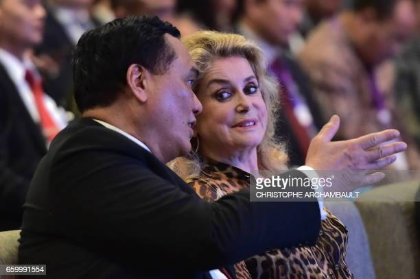 French actress Catherine Deneuve listens to an official during creative economy gathering with French President Francois Hollande in Jakarta on March...