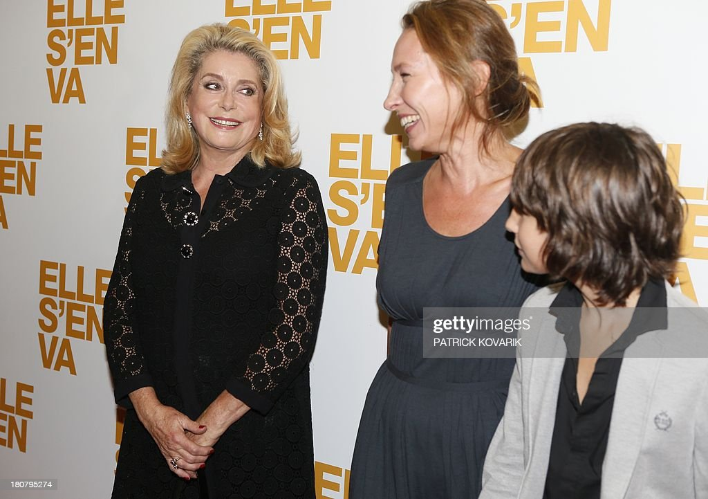 French actress Catherine Deneuve poses flanked by director Emmanuelle Bercot and actor Nemo Schiffman prior to attend the Premiere of their new movie 'Elle s'en va' ('On my way'), on September 16, 2013 in Paris. AFP PHOTO / PATRICK KOVARIK