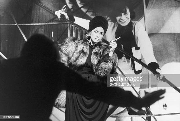 French actress Catherine Deneuve wearing fashions by Yves Saint Laurent and posing in front of a photo of Coco Chanel at a photoshoot by German...