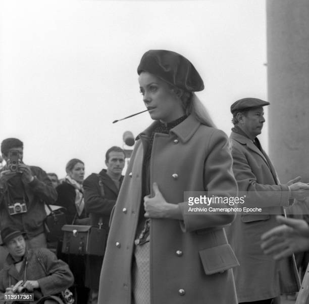 French actress Cathrine Deneuve on the set of the movie 'Mayerling' wearing a coat and and a beret a paintbrush in her mouth with photographer behind...