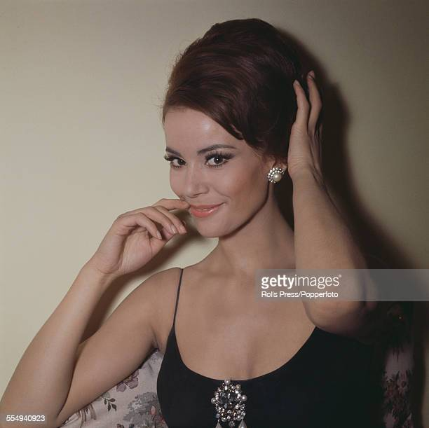 French actress Claudine Auger who plays the role of Domino Derval in the James Bond film 'Thunderball' posed wearing pearl ear rings and brooch circa...