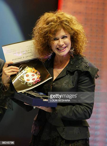 French actress Corinne Clery holds her lifetime achievement award during the opening ceremony of the 14th Damascus International Film Festival late...