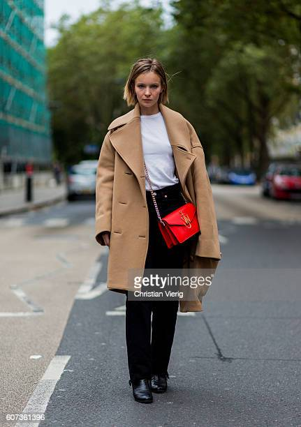 French actress Diane Rouxel wearing a red JW Anderson bag and beige wool coat outside of JW Anderson during London Fashion Week Spring/Summer...