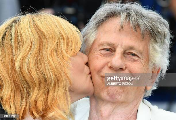 French actress Emmanuelle Seigner kisses FrenchPolish director Roman Polanski on May 27 2017 during a photocall for the film 'Based on a True Story'...