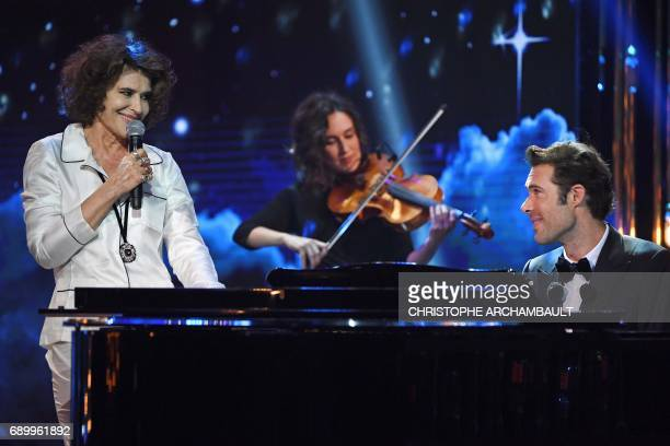 French actress Fanny Ardant and host Nicolas Bedos sing at the end of the French theatre awards 'Molieres' ceremony at the Folies Bergeres Theatre in...