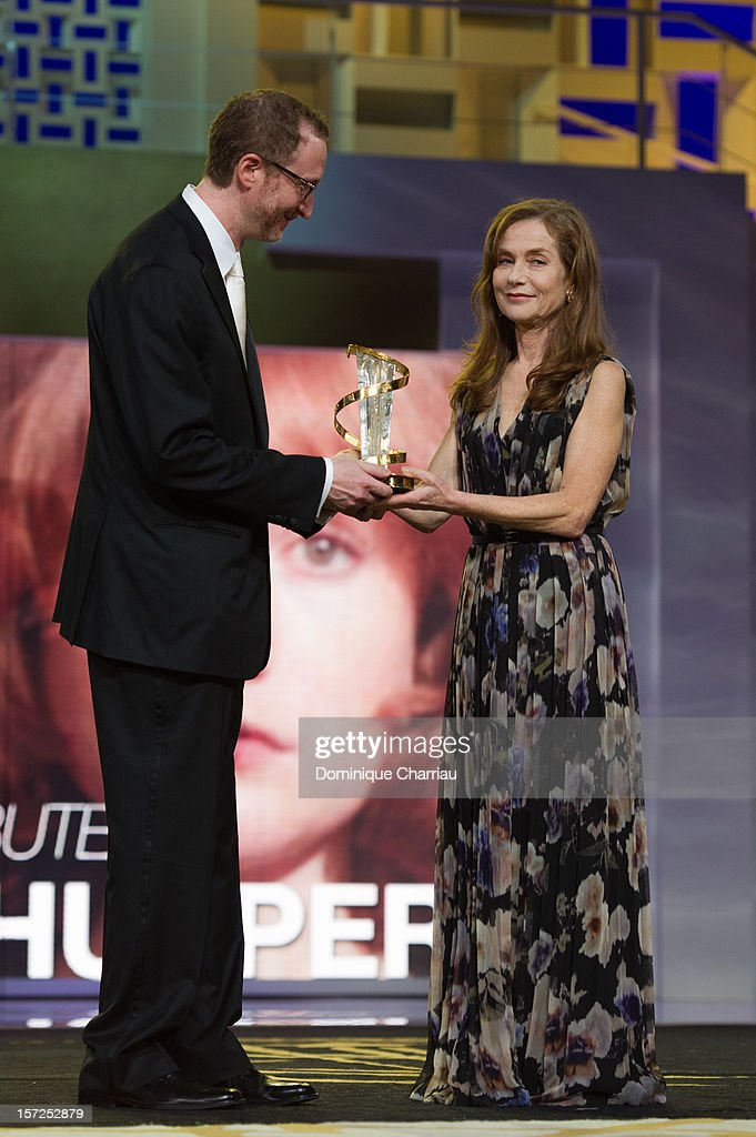 French Actress <a gi-track='captionPersonalityLinkClicked' href=/galleries/search?phrase=Isabelle+Huppert&family=editorial&specificpeople=662796 ng-click='$event.stopPropagation()'>Isabelle Huppert</a> awarded by James gray during her tribute during the opening ceremony of the 12th Marrakech International Film Festival on November 30, 2012 in Marrakech, Morocco.