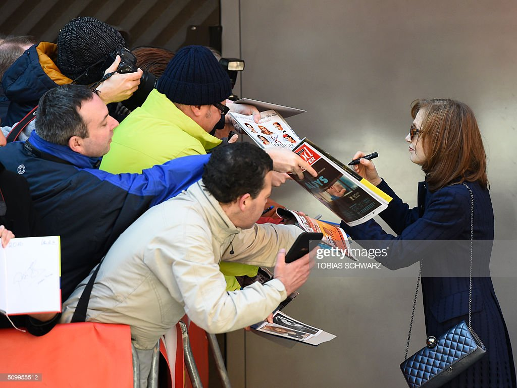 French actress Isabelle Huppert sign autographs ahead a photo call for the film 'L'Avenir' (Things to Come) in competition at the 66th Berlinale Film Festival in Berlin on February 13, 2016. / AFP / TOBIAS SCHWARZ