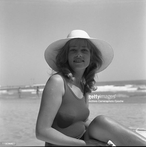 French actress Jeanne Moreau portrayed wearing a swimming suit and a widebrimmed hat the seashore and some people in the background Lido beach Venice...