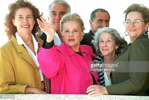 French actress Jeanne Moreau salutes photographers as she is surrounded by members of the jury of the Cannes Film Festival at the Cannes Festival...