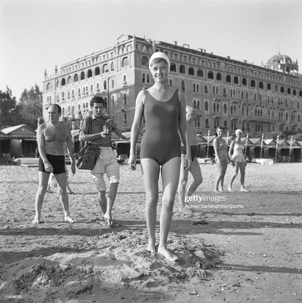 French actress Jeanne Moreau wearing a swimming suit and a cap standing on the Lido beach in front of the Hotel Excelsior people behind them and a...