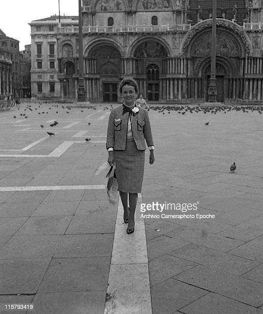 French actress Jeanne Moreau wearing a tailleur and holding a bag walking in an empty St Mark Square St Mark's basilica in the background during the...