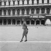 French actress Jeanne Moreau wearing a tailleur and holding a bag portrayed from the side in an empty St Mark Square during the Movie Festival a...