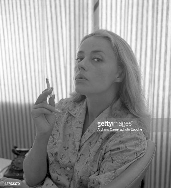 French actress Jeanne Moreau wearing an embroidered shirt portrayed while smoking a cigarette and blowing smoke out a telephone and a striped curtain...