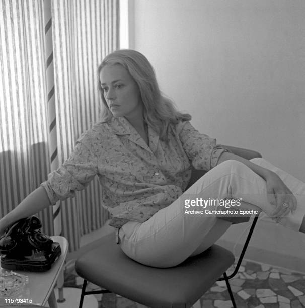 French actress Jeanne Moreau wearing an embroidered shirt portrayed sitting by the side on a chair a striped curtain the background a telephone and...