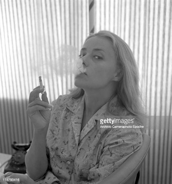 French actress Jeanne Moreau wearing an embroidered shirt portrayed while smoking a cigarette and blowing smoke spirals out a striped curtain and a...