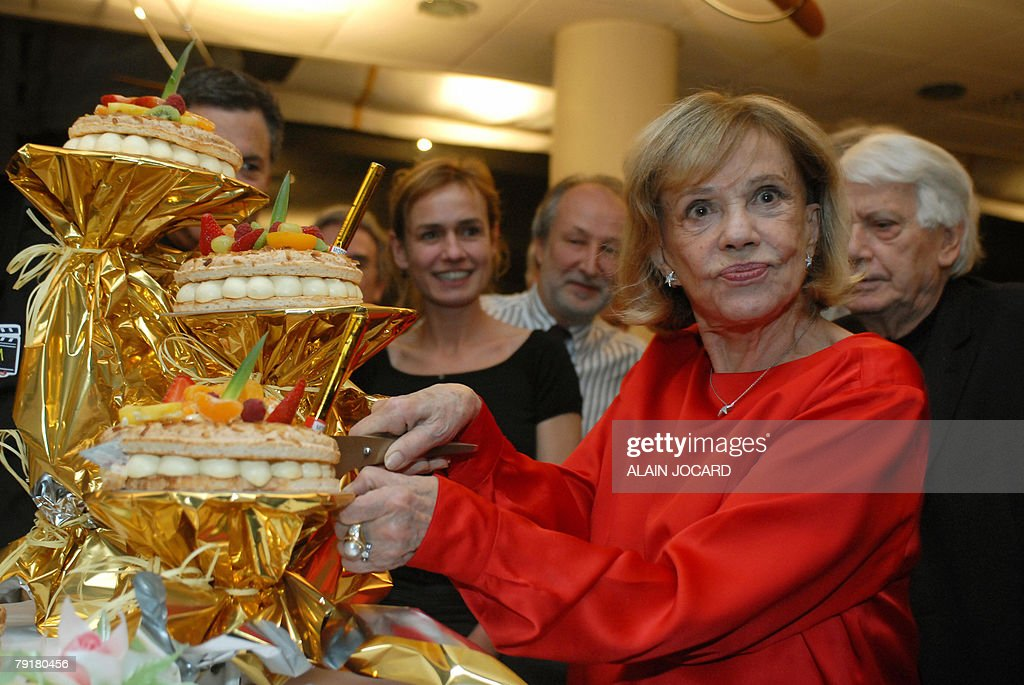 French actress Jeanne Moreau, who celebrates today her 80th birthday, cuts a share of her birthday cake flanked by French actress Sandrine Bonnaire (C), 23 January 2008 in Angers, during the 20th edition of the Festival Premiers Plan (Festival of cinema).