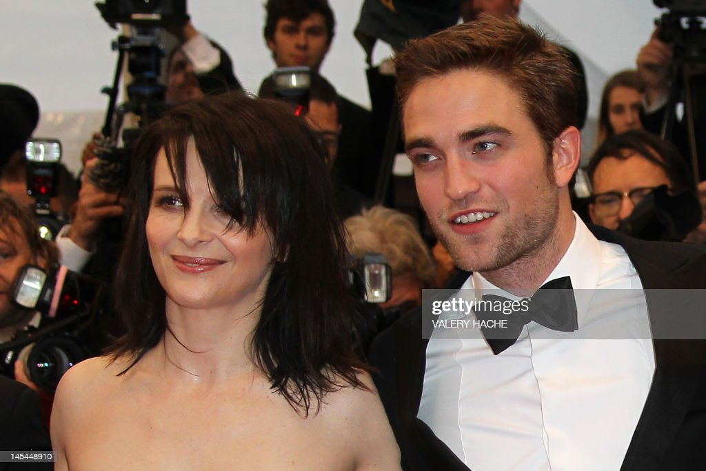 French actress Juliette Binoche and British actor Robert Pattinson pose as they arrive for the screening of their film 'Cosmopolis' presented in competition at the 65th Cannes film festival on May 25, 2012 in Cannes. AFP PHOTO / VALERY HACHE