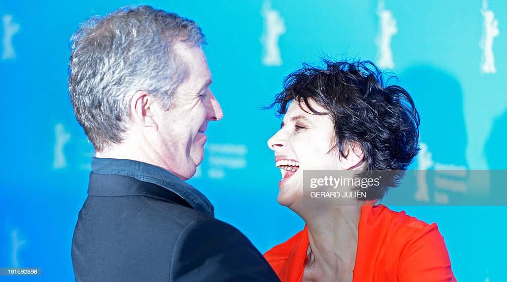 French actress Juliette Binoche shares a joke with French director Bruno Dumont (L) during a photocall for the premiere of the film 'Camille Claudel 1915' presented in the Berlinale Competition of the 63rd Berlin International Film Festival in Berlin on February 12, 2013. AFP PHOTO / GERARD JULIEN