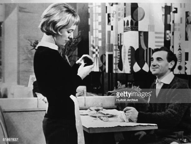 French actress Marie Dubois opens a jewelry box as French actor Charles Aznavour seated at a dinner table watches with a smile on his face in a scene...