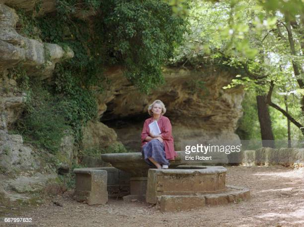 French actress MarieChristine Barrault sits at the edge of an old stone fountain in the village of Grignan in the Drome region of France She is...