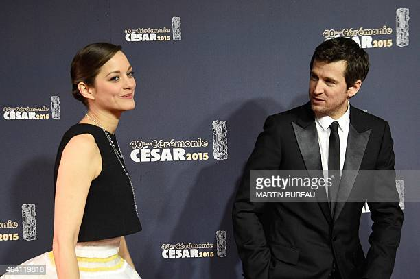 French actress Marion Cotillard and her partner French actor Guillaume Canet pose as they arrive for the 40th edition of the Cesar Awards ceremony on...