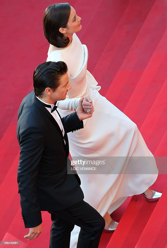 French actress Marion Cotillard (R) and US actor Jeremy Renner arrive on May 24, 2013 for the screening of the film 'The Immigrant' presented in Competition at the 66th edition of the Cannes Film Festival in Cannes. Cannes, one of the world's top film festivals, opened on May 15 and will climax on May 26 with awards selected by a jury headed this year by Hollywood legend Steven Spielberg. AFP PHOTO / LOIC VENANCE