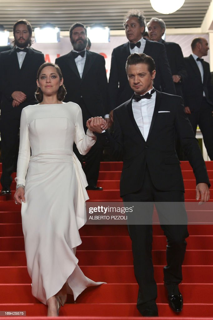 French actress Marion Cotillard (L) and US actor Jeremy Renner leave on May 24, 2013 after attending the screening of the film 'The Immigrant' presented in Competition at the 66th edition of the Cannes Film Festival in Cannes. Cannes, one of the world's top film festivals, opened on May 15 and will climax on May 26 with awards selected by a jury headed this year by Hollywood legend Steven Spielberg. AFP PHOTO / ALBERTO PIZZOLI