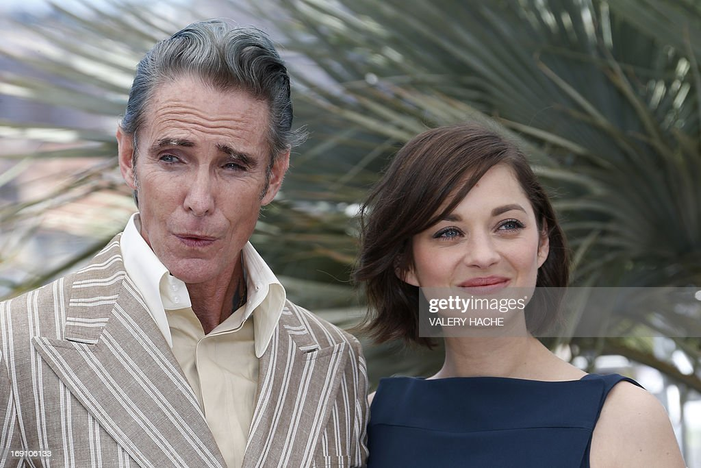 French actress Marion Cotillard (R) and US tattoo artist and actor Mark Mahoney pose on May 20, 2013 during a photocall for the film 'Blood Ties' presented Out of Competition at the 66th edition of the Cannes Film Festival in Cannes. Cannes, one of the world's top film festivals, opened on May 15 and will climax on May 26 with awards selected by a jury headed this year by Hollywood legend Steven Spielberg.
