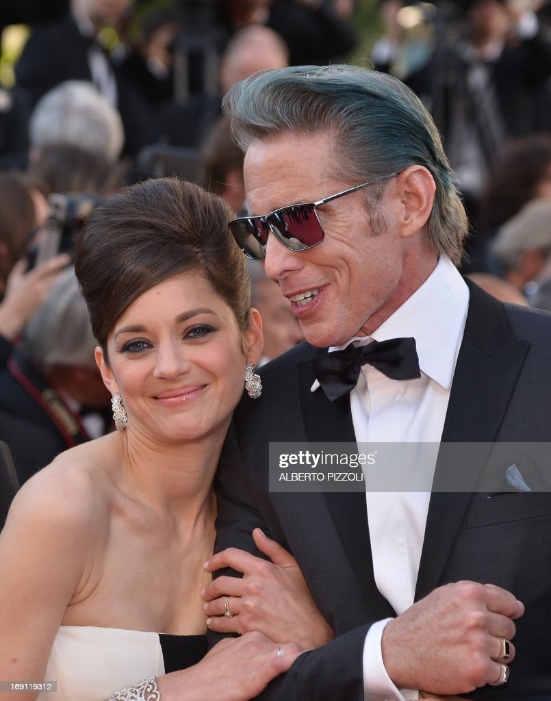 French actress Marion Cotillard (L) and US tattoo artist and actor Mark Mahoney arrive on May 20, 2013 for the screening of the film 'Blood Ties' presented Out of Competition at the 66th edition of the Cannes Film Festival in Cannes. Cannes, one of the world's top film festivals, opened on May 15 and will climax on May 26 with awards selected by a jury headed this year by Hollywood legend Steven Spielberg. AFP PHOTO / ALBERTO PIZZOLI