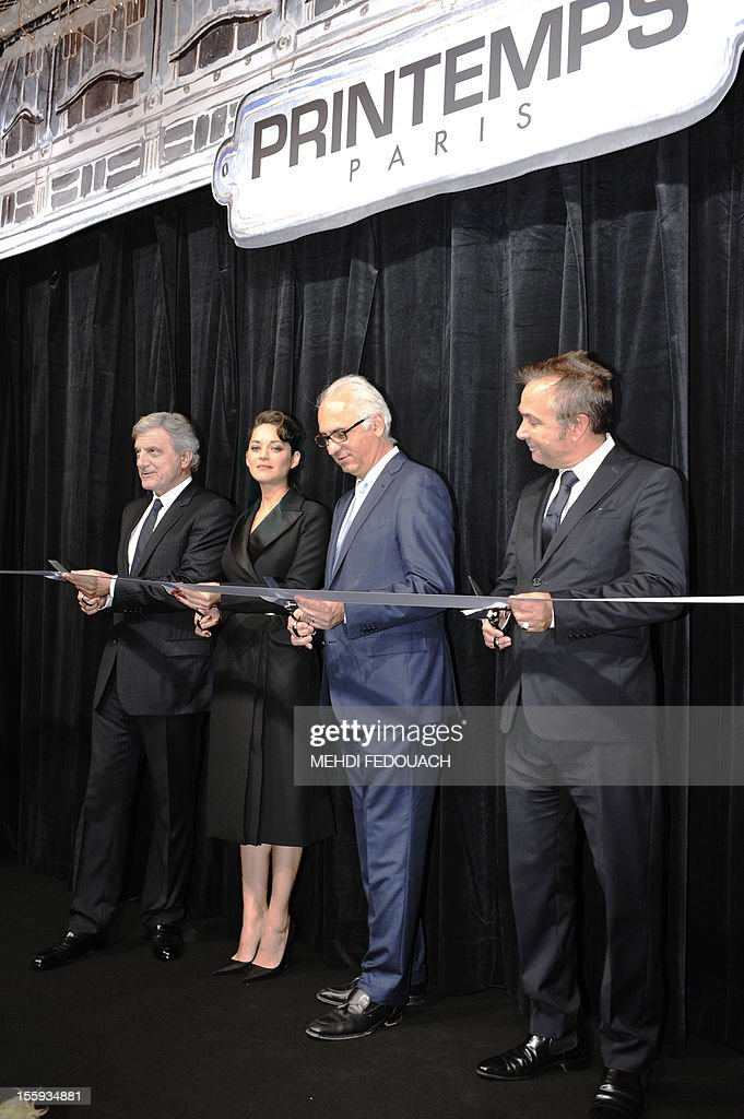 French actress Marion Cotillard (2nd L) cuts an inaugural ribbon with Printemps store CEO Paolo De Cesare (2nd R) and the CEO of Christian Dior Couture Sidney Toledano (L) inside the Printemps department store during the launch of the new Christmas season displays on November 9, 2012, in Paris. AFP PHOTO / MEHDI FEDOUACH