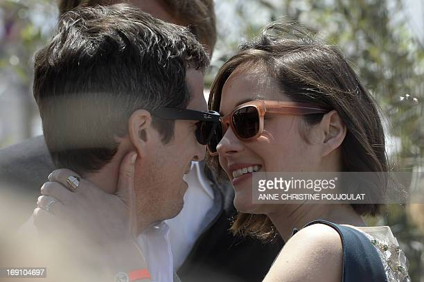 French actress Marion Cotillard hugs her partner French director Guillaume Canet on May 20 2013 before attending a photocall for the film 'Blood...