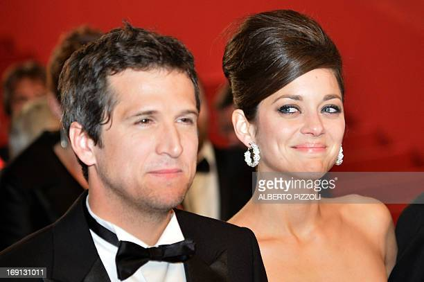 French actress Marion Cotillard looks at her partner director Guillaume Canet on May 20 2013 as they leave after attending the screening of the film...